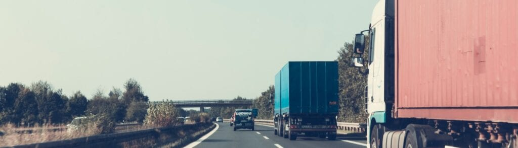 Canva Person Driving on Road Beside Trailer Trucks 1500x430 1