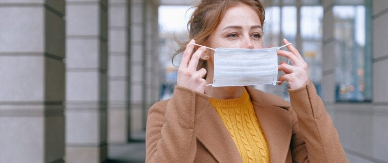 woman putting on face mask to screen visitors for COVID-19