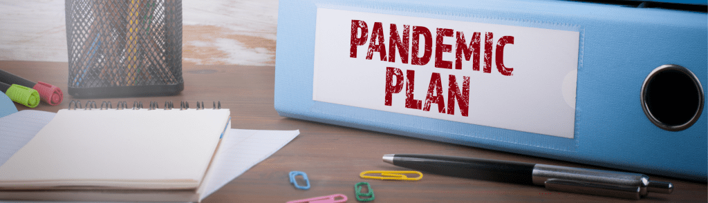 binder on a desk with papers and pens with a label saying pandemic plan indicating an updated health and safety plan